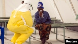 A health worker wearing protective gear attends to a newly admitted suspected Ebola patient in a quarantine zone at a Red Cross facility in the town of Koidu, Kono district in Eastern Sierra Leone, Dec. 19, 2014.