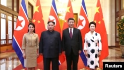 Pemimpin Korea Utara Kim Jong Un dan istrinya Ri Sol Ju berfoto bersama dengan Presiden China, Xi Jinping dan istri Peng Liyuan di Balai Besar Rakyat di Beijing, China, 28 Maret 2018.(Foto: Ju Peng/Xinhua via REUTERS).