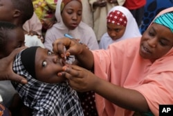 FILE - A health official administers a polio vaccine to a child in Kawo Kano, Nigeria, April 13, 2014. Vaccination campaigns have resumed this year after the disease resurfaced.