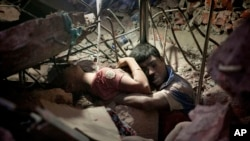 FOR USE AS DESIRED, YEAR END PHOTOS - FILE - A Bangladeshi man holds on to a woman, both victims of a building collapse, in the debris of Rana Plaza garment factory in Savar near Dhaka, Bangladesh, April 25, 2013. The collapse of Rana Plaza in Dhaka that