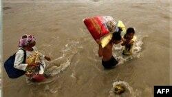 Nạn nhân lũ lụt lội qua 1 con sông sau khi nhận hàng cứu trợ tại thành phố Iligan, miền nam Philippines, Chủ nhật 25/12/2011