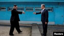 Pemimpin Korut Kim Jong Un (kiri) dan Presiden Korsel Moon Jae-in ketika bertemu di Panmunjom 27 April 2018.