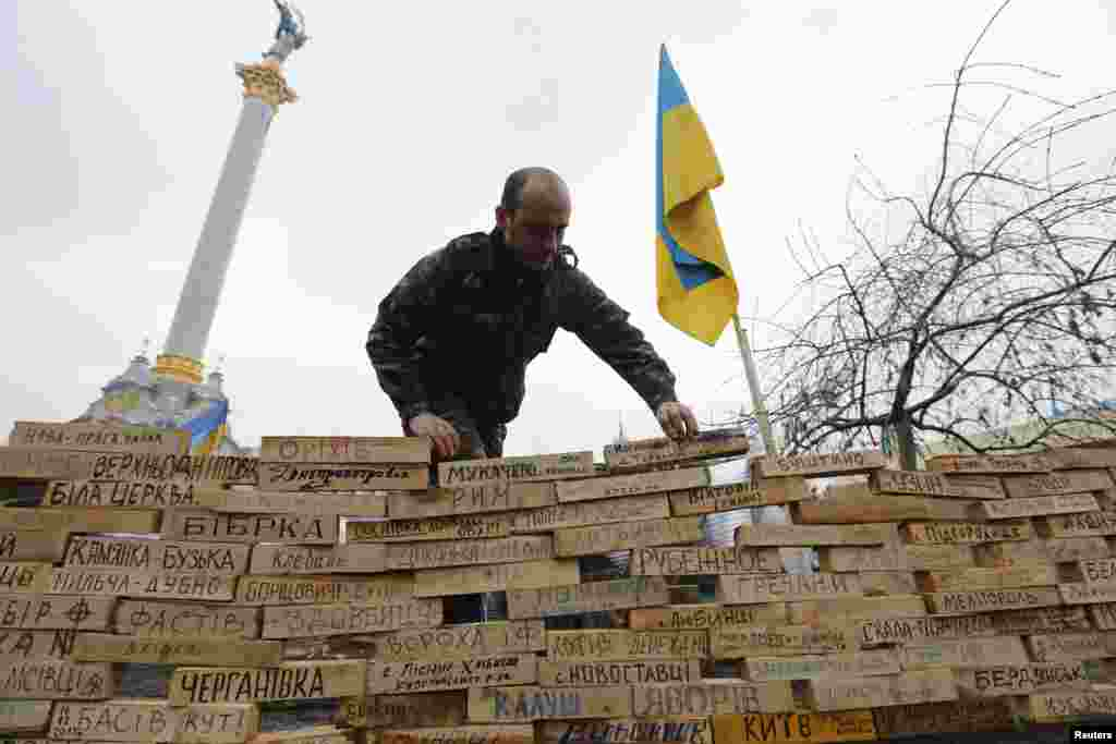 A man stacks wooden bars showing names of Ukrainian cities and settlements that are hometowns of demonstrators, during a rally in Independence Square in Kyiv, Dec. 16, 2013.