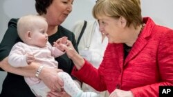 FILE - German chancellor Angela Merkel sshares a smile with the ten-month-old baby Romy at an event celebrating the 15th anniversary of the family support organization 'Wellcome ' in Berlin, March 6, 2017.