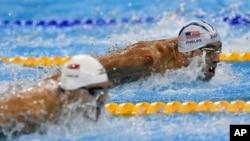 Michael Phelps (atas) beradu dengan Joseph Schooling dari Singapura dalam kompetisi gaya kupu-kupu 100-meter putra di Olimpiade Rio 2016.