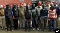 Polisi India bersama 6 anggota gang di negara bagian Punjab (ditutup mukanya) yang menjadi tersangka pelaku perkosaan terbaru terhadap penumpang bis (13/1).