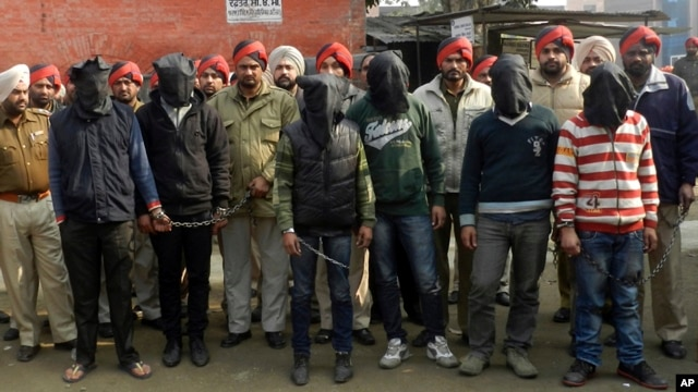 Indian policemen stand with six men, face covered in black sheet, suspected in a gang rape of a bus passenger in Punjab state, India, January 13, 2013.