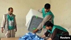 د افغانستان د انتخاباتو کارکوونکي له رایو پاڼو صندقونه تشوي.