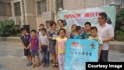 公益教育志愿者珍珠(左四)与山区孩子接受图书捐赠