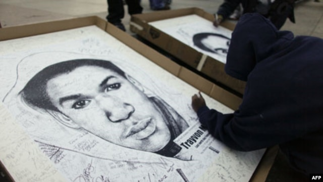 A supporter signs his name to a poster for Trayvon Martin