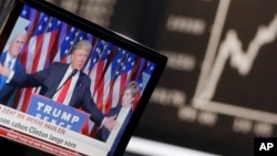 FILE - US President-elected Donald Trump is displayed on a television screen with the curve of the German stock index DAX in background at the stock market in Frankfurt, Germany, Nov. 9, 2016.