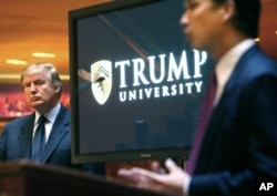 FILE- In this May 23, 2005, file photo, real estate mogul and reality TV star Donald Trump, left, listens as Michael Sexton introduces him at a news conference in New York where he announced the establishment of Trump University.