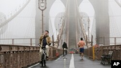 Bicyclists and a jogger cross the Brooklyn Bridge in a heavy fog Dec. 23, 2015, in New York. A weather pattern partly linked with el Nino has turned winter upside-down across the US.