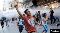 Demonstran anti-pemerintah berlarian menghindari semprotan meriam air yang ditembakkan oleh polisi anti huru-hara di jalan utama Istiklal di pusat kota Istanbul (3/8).
