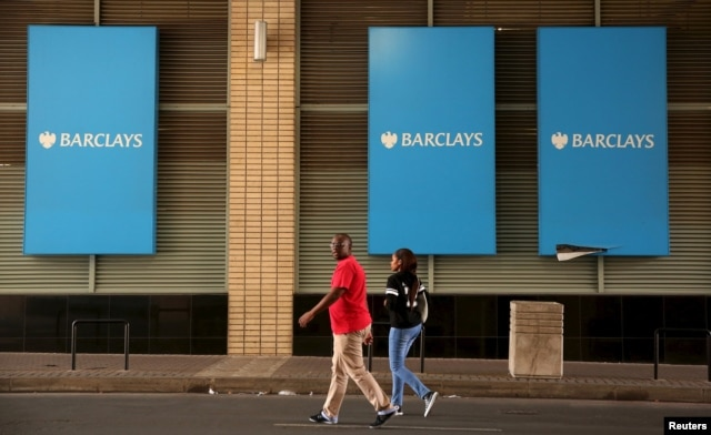 A couple walks past a Barclays logo in Johannesburg, South Africa, Dec. 16, 2015.