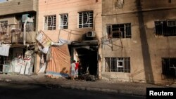 Anak-anak laki-laki tengah memeriksa lokasi terjadinya serangan bom di wilayah Tobchi, Baghdad (21/7). Sedikitnya 46 orang dilaporkan tewas dalam gelombang serangan bom mobil di beberapa kawasan kota Baghdad, Sabtu malam.