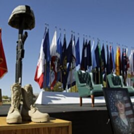 A soldier's memorial and photos are seen during a Remembrance Ceremony commemorating the one-year anniversary of the worst mass shooting on a U.S. military base, where 13 people were killed and dozens wounded, Friday, Nov. 5, 2010, in Fort Hood. (AP Photo