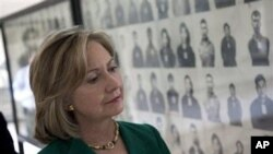 US Secretary of State Hillary Rodham Clinton looks at a wall of faces of those killed by the Khmer Rouge regime, during a tour of the Tuol Sleng Genocide Museum, formerly the regime's notorious S-21 prison, on Monday.