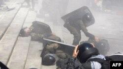 31일 우크라이 키예프의 의회 건물 앞에서 헌법 개정안에 반대하는 시위가 발생한 가운데, 진압 경찰이 부상당한 동료를 부축하고 있다.