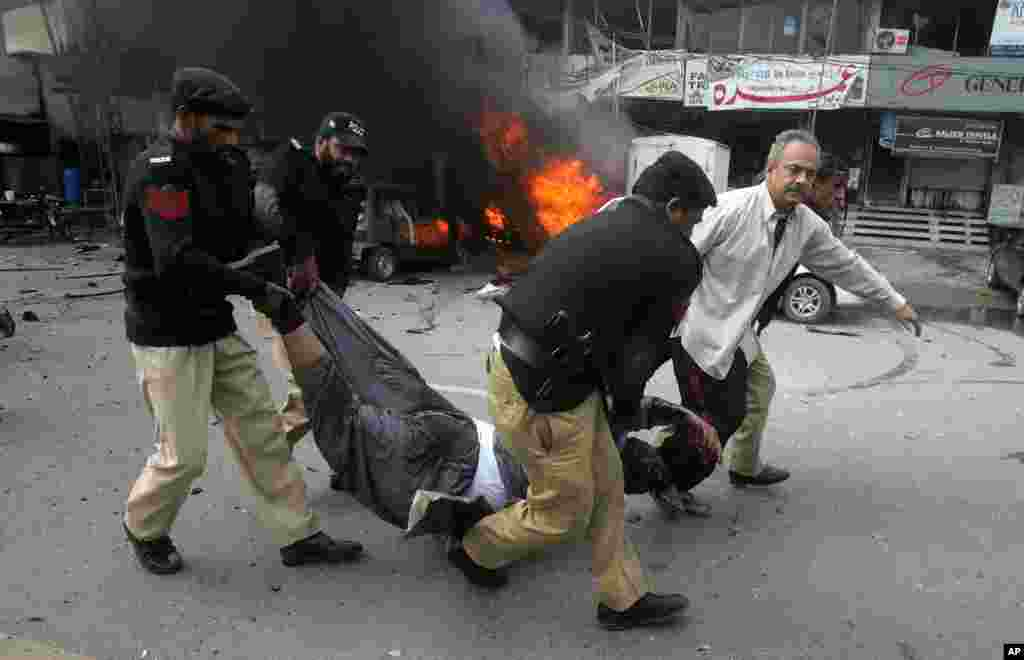 Pakistani police officers and a volunteer rush an injured person to a hospital after a bombing in Lahore, Pakistan, Feb. 17, 2015.
