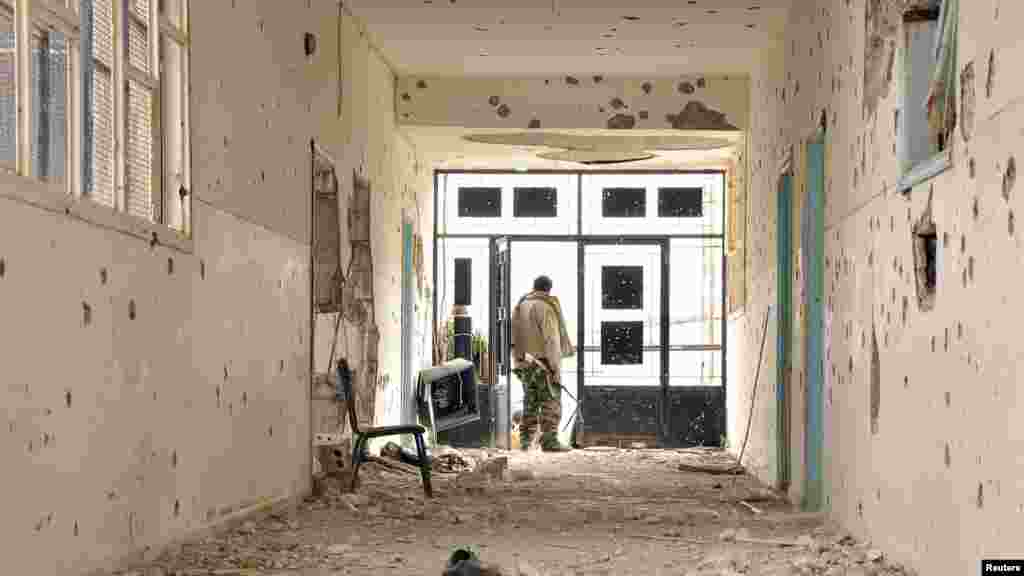 A Kurdish People's Protection Units fighter stands in a damaged school in Al-Menajir village, Ras Al-Ain countryside, Syria, Jan. 26, 2014.