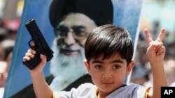 FILE - An Iraqi boy living in Iran holds a toy gun and flashes a victory sign in front of a poster of Iranian supreme leader Ayatollah Ali Khamenei in demonstration against Sunni militants of the Islamic State group in Tehran, June 20, 2014.