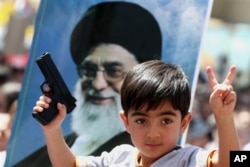 FILE - An Iraqi boy living in Iran holds a toy gun and flashes a victory sign in front of a poster of the Iranian Supreme leader Ayatollah Ali Khamenei in demonstration against Islamic State of Iraq and the Levant, Tehran, June 20, 2014.