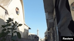 A resident walks on a damaged street in Hamidiyeh, Homs, Syria, July 1, 2012.