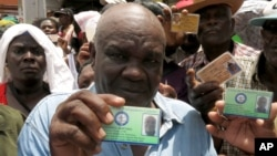 Haitian Jaquenol Martinez shows a card that proves that he has worked in the Dominican sugar cane fields since 1963, while trying to apply for a temporary resident permit, in Santo Domingo, Dominican Republic, June 15, 2015.