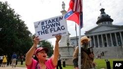 Seorang aktivis mengacungkan tanda yang mendukung penurunan bendera dari ibukota South Carolina (9/7).