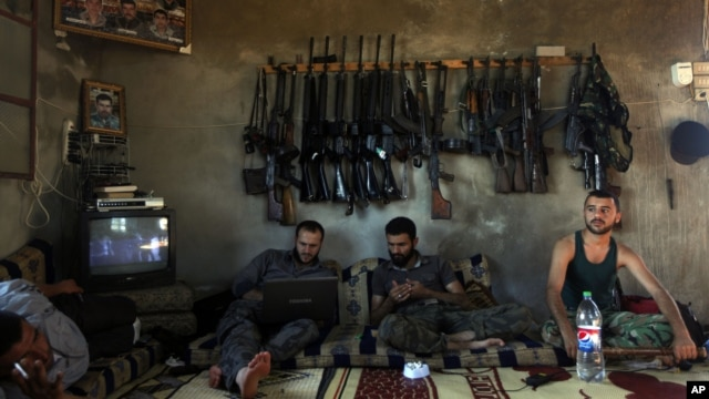 Free Syrian Army fighters sit in a house on the outskirts of Aleppo June 12, 2012.