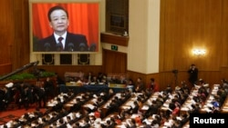 China's Premier Wen Jiabao (shown on screen) speaks as delegates listen during the opening ceremony of National People's Congress (NPC) at the Great Hall of the People in Beijing, March 5, 2013.