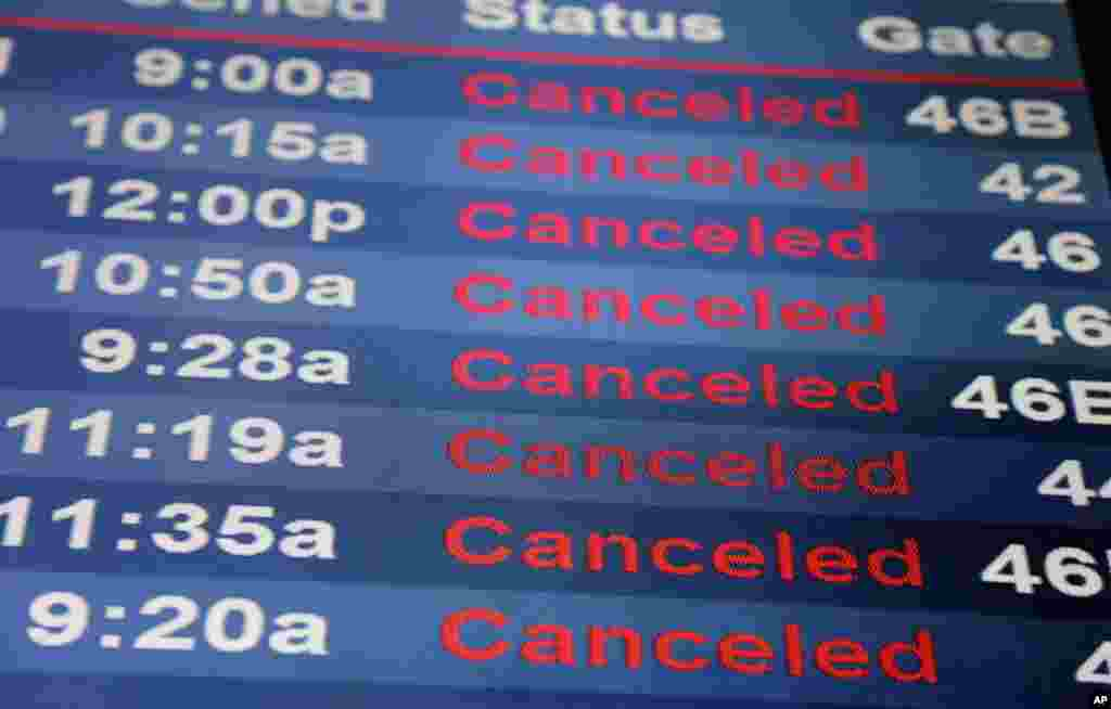 Screens display canceled flights at Newark Liberty International Airport in Newark, New Jersey, March 14, 2017. A storm pounded the Northeast with more than a foot of snow in places, paralyzing much of the Washington-to-Boston corridor.
