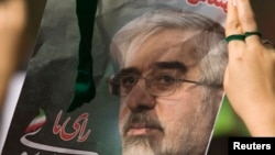 FILE - An Iranian woman holds a picture of defeated presidential candidate and opposition leader Mirhossein Mousavi during a rally marking Qods (Jerusalem) Day in Tehran, September 18, 2009.