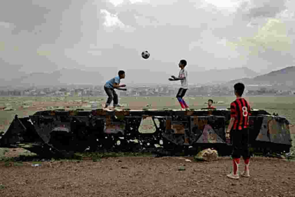 En Kabul, niños afganos juegan a la pelota sobre los restos de un vehículo militar ruso.