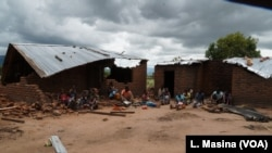 Victims of mob attacks sitting outisde their demolished houses on suspicion that they are withholding rains.