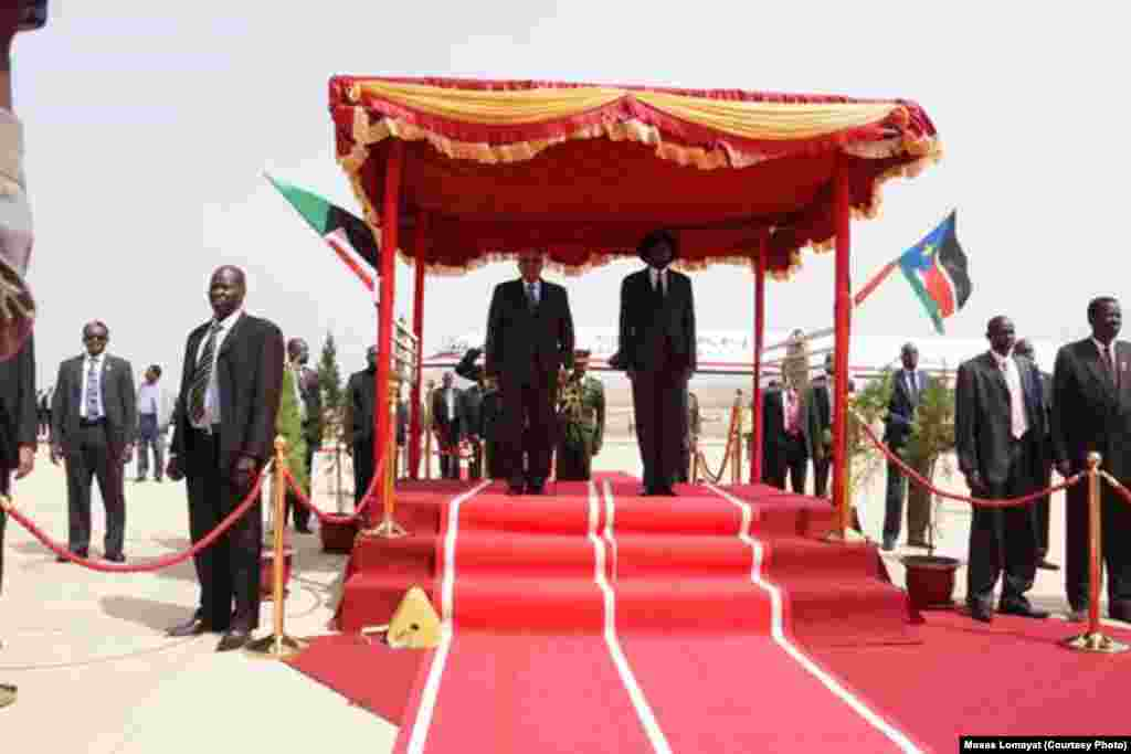 The presidents of Sudan and South Sudan stand to attention, side-by-side, as the national anthems of their countries play at Juba airport on Friday, April 12, 2013 at the start of the first visit by Sudanese President Omar al Bashir to South Sudan.