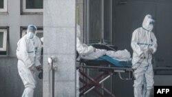 Des membres du personnel médical transportent un patient à l'hôpital de Jinyintan, où des patients infectés par un mystérieux virus semblable au SRAS sont traités, à Wuhan dans la province centrale du Hubei en Chine le 18 janvier 2020. (Photo by STR / AFP)