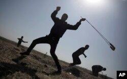 یو فلسطینی د اسرائیلي سرتیرو په لور ډبرې ورغورځوي.