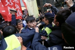 FILE - Hong Kong democracy activist Joshua Wong and others scuffle with police as they protest during the election for Hong Kong's next chief executive near the venue where the vote is taking place in Hong Kong, March 26, 2017.