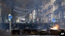 Los manifestantes están parados detrás de un cubo en llamas durante los enfrentamientos, el sábado 8 de diciembre de 2018 en Marsella, en el sur de Francia.