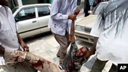 Somali man is carried away from scene of suicide bomb attack during university student graduation ceremony at a local hotel in Mogadishu, 3 Dec 2009