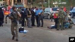 Lực lượng an ninh Kenya và các nhân viên sứ quán Mỹ đứng gần thi thể người đàn ông bị bắn chết bên ngoài Đại sứ quán Hoa Kỳ ở Nairobi, Kenya, 27/10/2016.