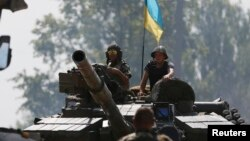 Ukrainian soldiers look out from a tank at a position some 40 miles from the eastern Ukrainian city of Donetsk, July 10, 2014.