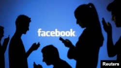 People are silhouetted as they pose with laptops in front of a screen projected with a Facebook logo, file photo.
