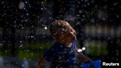 Seorang anak bermain air untuk mendinginkan dari cuaca panas ekstrem di Washington DC, 20 Juli 2019. (Foto: Reuters)