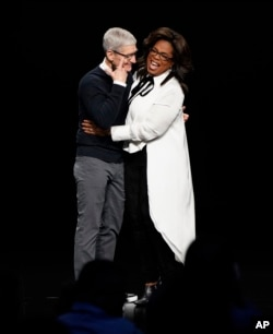 Apple CEO Tim Cook and Oprah Winfrey embrace at the Steve Jobs Theater during an event to announce new Apple products Monday, March 25, 2019, in Cupertino, Calif. (AP Photo/Tony Avelar)