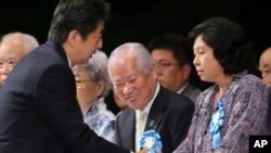 FILE - Japan's Prime Minister Shinzo Abe, left, shakes hands with former abductee Hitomi Soga. (AP Photo/Koji Sasahara)