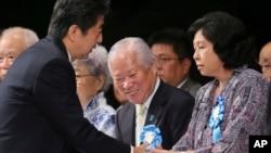 아베 신조 일본 총리(왼쪽)가 지난해 9월 일본의 납북자 피해 가족들과 만나, 문제 해결을 위한 정부의 노력을 약속하고 있다. (자료사진)