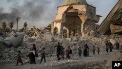 4일 이라크 모술 올드시티 주민들이 정부군과 ISIL 간 교전으로 폐허가 된 도시를 빠져나고 있다. ISIL이 파괴한 '알누리 사원' 모습이 주민들 뒤로 보인다.